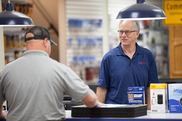 RHI employee working at sales desk helping HVAC/R customer.