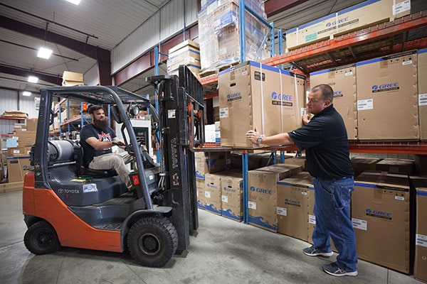 RHI Supply service staff loading HVAC equipment with forklift in warehouse for a customer.